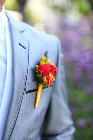 Wonderful wedding boutonniere on a costume of groom from beautiful colorful flowers. Nice bokeh in the background. Stock Photo