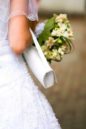 Beautiful wedding dress on a bride with veil, white handbag and beautiful bouquet in hands. photo