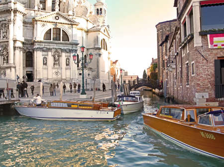 Heavy traffic of taxi boats on Grand Canal near famous Basilica di Santa Maria della Salute in Venice, Italy