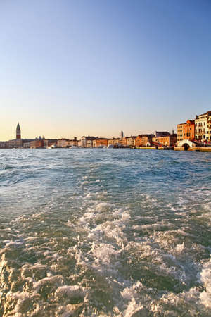 View from vaporetto to Grand Canal in Venice, Italy. Waves, sunset time, clear blue sky and Campanile San Marco in the background. Stock Photo - 12904838