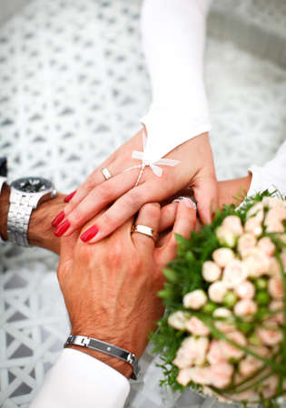Groom and bride are holding hand of each other with feelings of love. Luxury decoration like a bouquet from roses, golden wedding rings and beautiful manicure. Stock Photo - 13100855