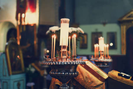Wedding accessories and interior in Saint Trinity Orthodox Convent including two candlesticks with many candles, flowers, icons and Holy Bible. Wonderful church in Riga, Latvia photo