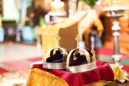 Two golden crown at wedding ceremony in beautiful interior of Saint Trinity Orthodox Convent in Riga, Latvia including candlesticks with many candles. Nice bokeh with copy space in the background. photo