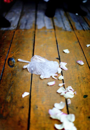 Cracked glass and plate in plastic package with many flower petals on a wooden floor. This is a wedding tradition. photo