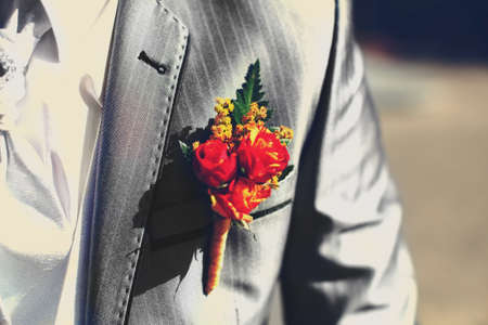 buttonhole: Wonderful wedding boutonniere on a costume of groom from beautiful colorful flowers.