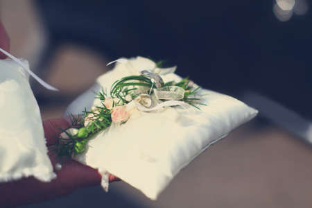 Wedding golden rings are holding in hand on white soft pillow from silk decorated with flowers. Stock Photo