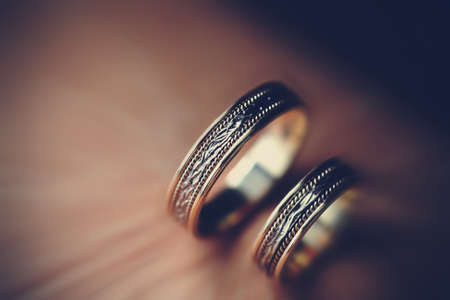 Closeup of two wedding golden rings with magnificent ornate decor on vintage background. Stock Photo