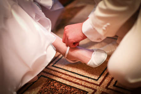 Groom in white costume is helping to wear classic wedding shoes on a bride before start of wedding ceremony. photo