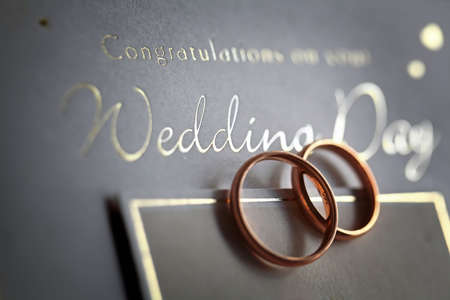 ring light: Classic golden rings on a silver wedding card with congratulations text.
