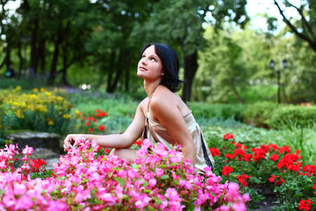 Sensual young lady is sitting into beautiful pink flowers in central park at summer day at Bastion hill in Riga, Latvia Stock Photo - 15831087