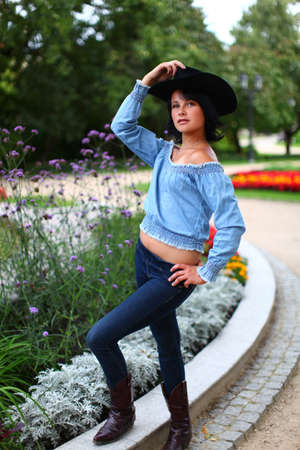 Young beautiful girl in country style with cowboy hat is standing at full length in summer park photo