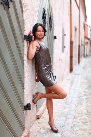 falda corta: Chica joven está de pie cerca de la puerta de madera vieja en pose sexual en toda su longitud en la calle del casco antiguo de Riga, Letonia Foto de archivo