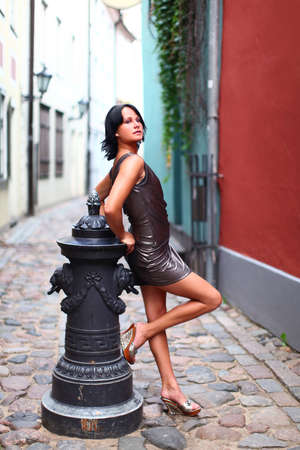 Gorgeous woman in beautiful dress is leaning with her back against old column in sexual and beautiful pose on the street of Old Riga, Latvia photo