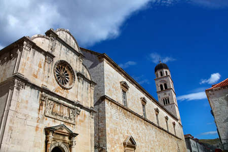 Franciscan Monastery in Dubrovnik at Stradun street with dramatic sky in background. Stock Photo