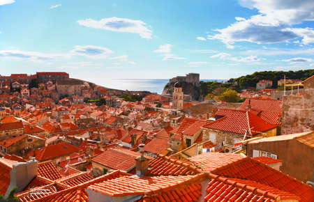View of many landmarks of Old town in city of Dubrovnik, Croatia. Classic red tiled rooftops with fortified wall around the city photo