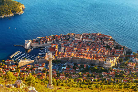 Amazing view from mountain at Old town of Dubrovnik in Croatia. Sunset in Adriatic sea, harbor with yachts, cable road, all is here. photo
