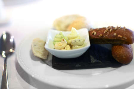 Plate with snacks from brown bread with sesame and four types of butter