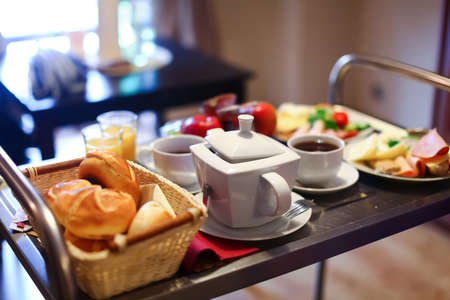 Morning breakfast  Served table with cups of hot tea, teapot, fresh bread, bun, croissant, plate with various cheese, ham, rolls, meat  Fruit mixed, orange juice, green salad, tomato