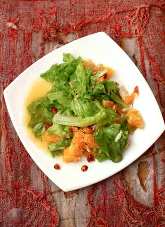 Chicken salad with oranges, almonds and honey on grunge ragged background Standard-Bild