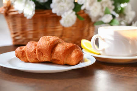 Croissant with hot cup of tea and lemon  Healthy morning breakfast