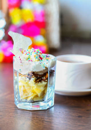Hot cup of tea and sweet fruit dessert with apples, walnut, lemon juice, whipped cream, cottage cheese, multi colored sugar sprinkles and caramel Stock Photo