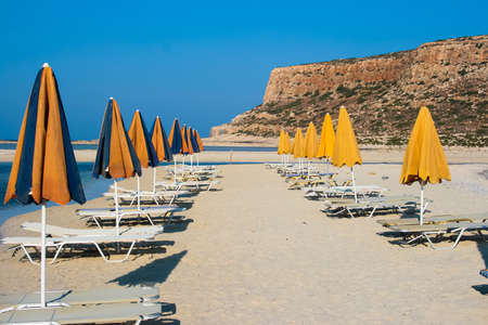 Sun umbrellas with sunbeds in beautiful Balos Lagoon and Gramvousa island on Crete, Greece  Cap tigani on the right
