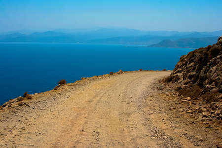 Mediterranean sea and gravel dangerous road, which leads to Gramvousa beach on island of Crete in Greece Standard-Bild