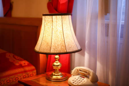 Vintage interior of luxury hotel room in retro style with decorated old lamp and telephone Standard-Bild