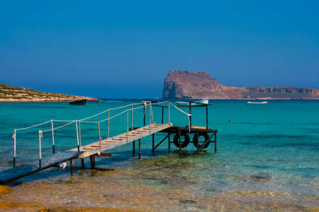 Pier with boats in Balos Lagoon and Gramvousa island on Crete, Greece