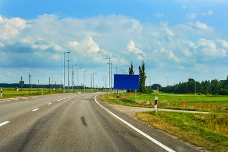 European route E67 it s part of Via Baltica road in countryside of Lithuania with beautiful clouds and fields Stock Photo