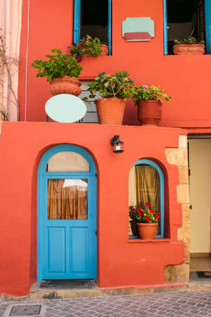 Colorful quiet backyard with beautiful flowers and classic traditional architecture in city of Chania on island of Crete, Greece