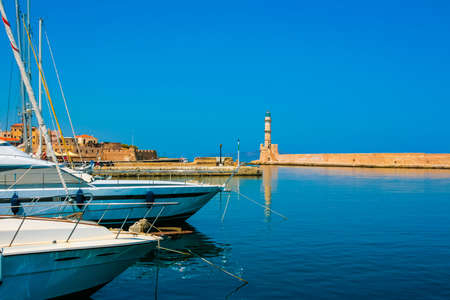 Lighthouse and yachts in Chania on island of Crete, Greece Stock Photo