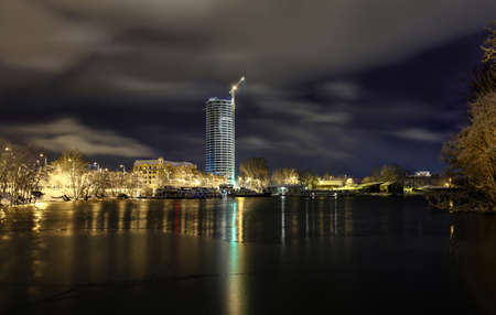 View of Riga, Latvia in winter night with skyscrapers and bay of Daugava river with beautiful clouds