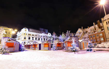 Livu square with Christmas market in a heart of Old Riga, Latvia at night with Russian Theater of Drama in a background