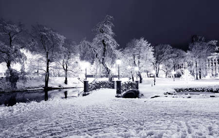 Winter night park with bridge and city channel in Old Riga, Latvia Stock Photo