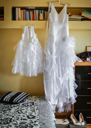 Bride's morning. Wedding dress for the bride and child hanging on the wall Standard-Bild - 131570218