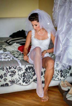 Bride's morning. Young bride is wearing sexy lingerie and stockings, veil and wedding dress. She's nervous, but happy! Standard-Bild