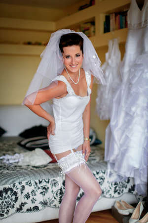Bride's morning. Young bride is wearing sexy lingerie and stockings, veil and wedding dress. She's smiling and happy Standard-Bild