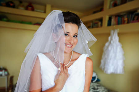 Bride's morning. Young bride is wearing veil and wedding dress. She's smiling and happy
