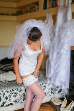 Bride's morning. Young bride is wearing sexy lingerie with garter belt, stockings, veil and wedding dress Standard-Bild - 132654712