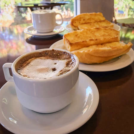Breakfast at Brazil with french bread toasted with butter on the plate with capuccino on table.