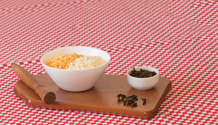 Brazilian dessert sweet canjica of yellow and white dry corn with clove in bowl and towel.