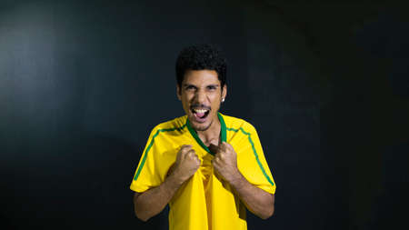 Male athlete or fan in yellow uniform worry or mad on black background concept image