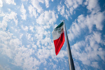 Mexican flag fluttering over a cloud sky on a sunny day.