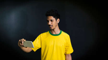 Male athlete or fan in yellow uniform looking cell phone on black background concept image.