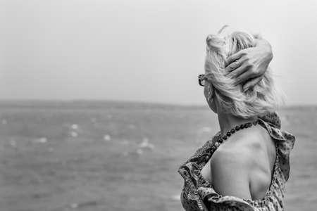 mujer mirando el horizonte: Mujer rubia que se aloja en la costa del mar y mirando hacia adelante hacia el horizonte