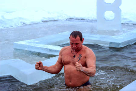 bathing man: A  robust man is bathing in an ice-hole on a frosty winter morning.