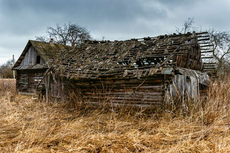 old barn in winter: Old abandoned wooden house with boarded up windows