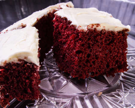 red velvet: A slice of red velvet cake with cream cheese frosting, ready to be eaten.