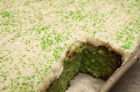 Green colored pistachio with white frosting and sugar sprinkles in a baking sheet. Imagens